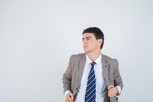 Jeune garçon tenant la main sur la veste en costume formel et à la confiance. vue de face.