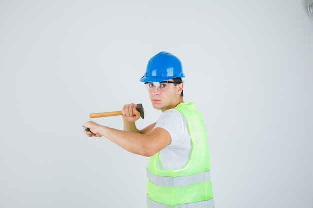 Jeune garçon tenant un marteau et un tournevis en uniforme de construction et à la confiance. vue de face.