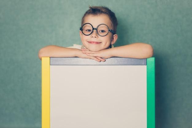 Jeune garçon tenant un tableau blanc blanc sur bleu