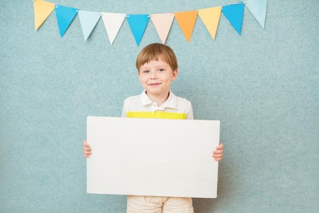 Jeune garçon tenant un tableau blanc blanc sur fond bleu