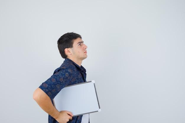 Jeune garçon tenant un tableau blanc en t-shirt blanc, chemise à fleurs et à la recherche de sérieux. vue de face.