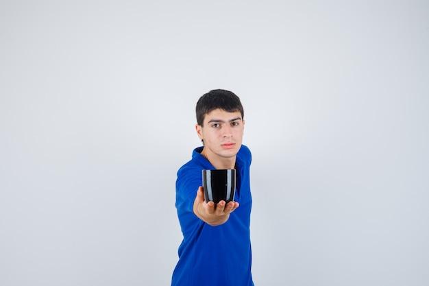Jeune garçon tenant la tasse, le donnant à quelqu'un en t-shirt bleu et à la vue sérieuse, de face.