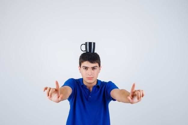 Jeune garçon tenant une tasse sur la tête, levant les index en t-shirt bleu et à la recherche de sérieux. vue de face.