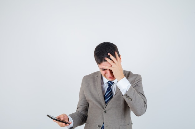 Jeune garçon tenant le téléphone, mettant la main sur la tête en costume formel et à la harcèlement. vue de face.