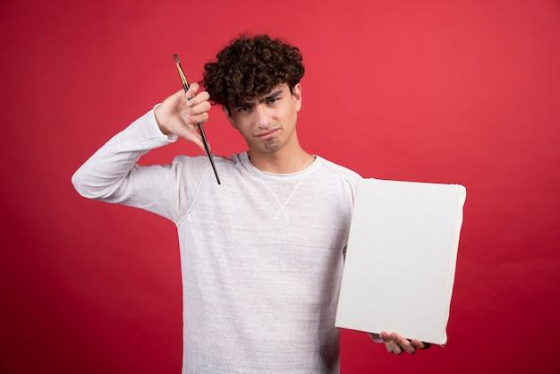 Jeune garçon tenant une toile vide et un pinceau