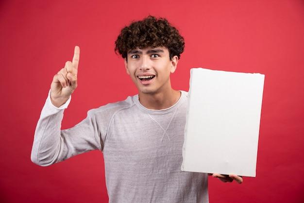 Jeune garçon tenant une toile vide