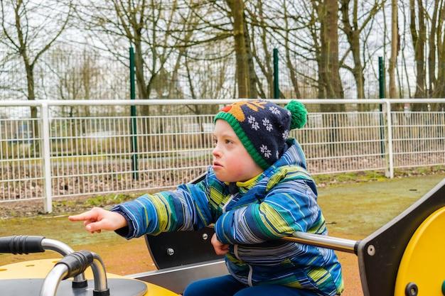 Jeune garçon trisomique jouant dans une cour de récréation