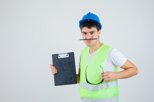 Jeune garçon en uniforme de construction tenant le presse-papiers et les lunettes de sécurité dans les mains, tenant le stylo avec la bouche et regardant sérieusement, vue de face.