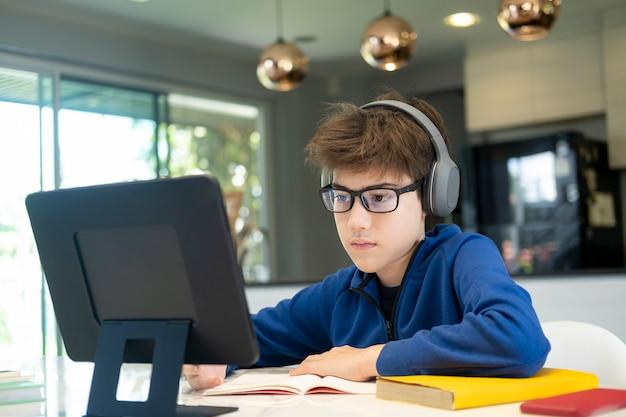 Jeune garçon utilisant un ordinateur et un appareil mobile étudiant en ligne. éducation et apprentissage en ligne.