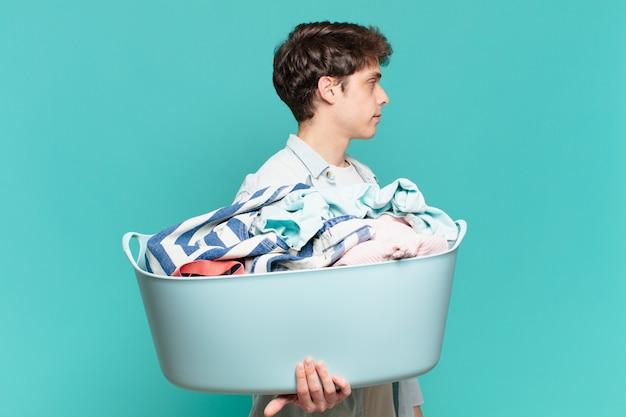 Jeune garçon en vue de profil cherchant à copier l'espace devant, pensant, imaginant ou rêvant le concept de lavage de vêtements
