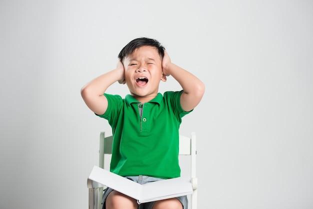 Jeune garçon et yeux fermés couvrant les oreilles avec les mains
