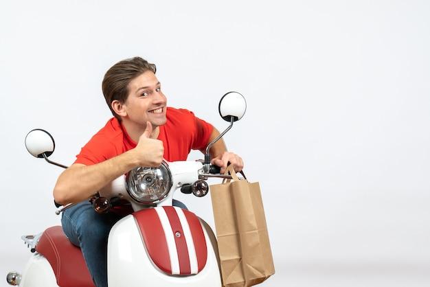 Jeune gars de courrier positif en uniforme rouge assis sur le scooter tenant des commandes et faisant un geste ok sur le mur jaune