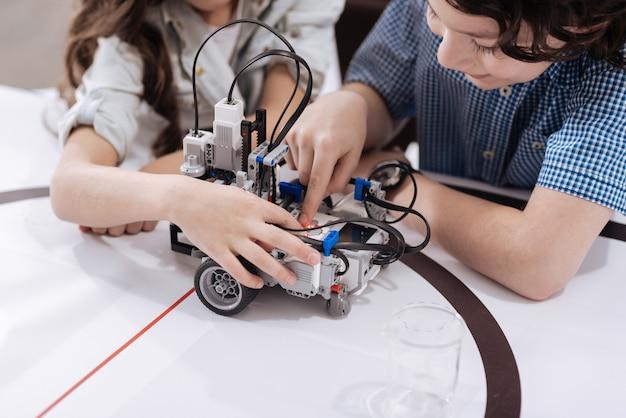 Jeune génération douée. des enfants impliqués intelligents et qualifiés assis dans le laboratoire et créant un robot tout en étudiant