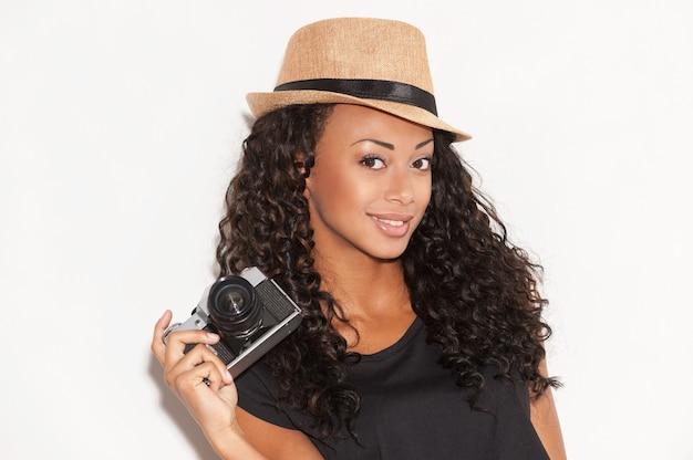 Jeune et génial. belle jeune femme africaine au chapeau funky tenant la caméra et souriant en se tenant debout sur fond blanc