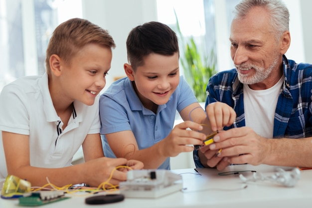 Jeune génie. beaux garçons positifs construisant un robot tout en profitant de l'ingénierie