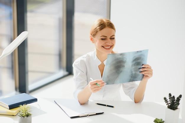 Jeune et gentil médecin regardant une radiographie du patient à l'hôpital