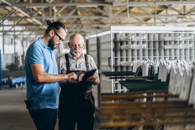 Jeune gestionnaire avec barbe montrant et inspectant le processus de travail d'un travailleur professionnel adulte sur la grande usine.