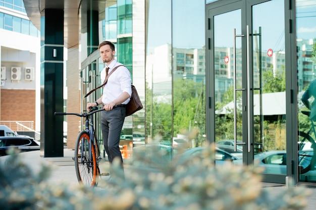 Jeune gestionnaire de bureau contemporain en tenue de soirée debout près de la porte du centre d'affaires tout en rentrant à la maison en vélo