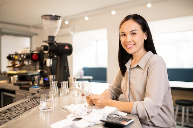 Jeune gestionnaire ou comptable de restaurant prospère avec tablette comptant les revenus à la fin de la journée de travail