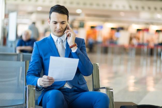 Jeune gestionnaire dans un aéroport en train de lire un document tout en parlant au téléphone
