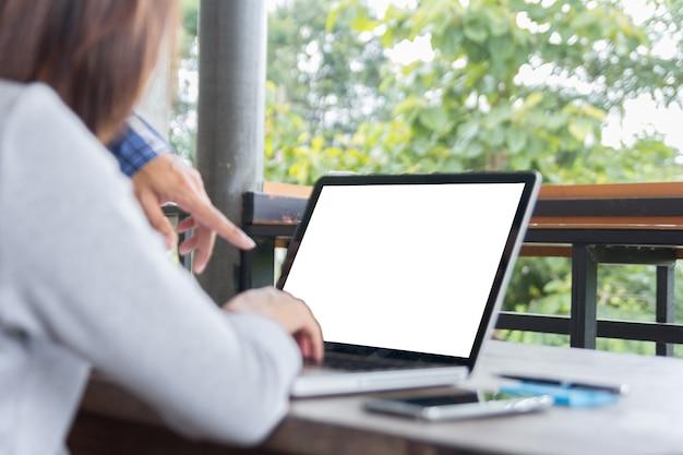 Jeune gestionnaire élégant aidant collègue avec des problèmes de travail pointant vers un écran d'ordinateur portable vide et expliquant les plans au bureau