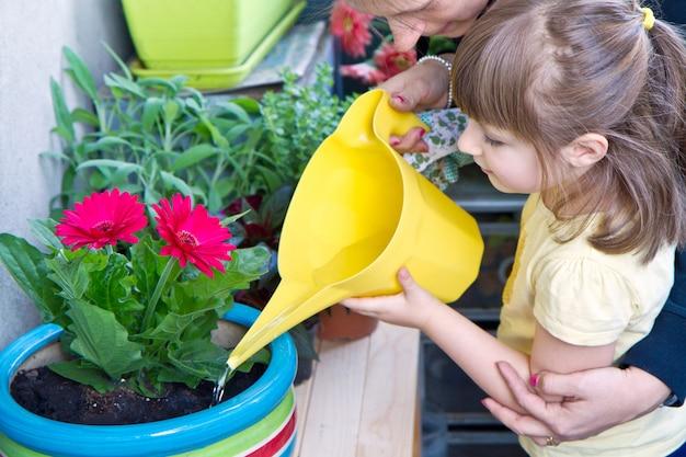 Jeune gil et mère arrosant une plante en pot souriant