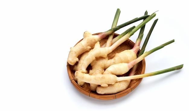 Jeune gingembre dans un panier en bambou sur fond blanc.