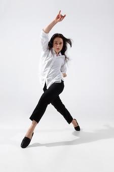Jeune et gracieuse danseuse de ballet dans un style noir minimal isolé sur fond de studio blanc