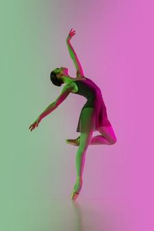 Jeune et gracieuse danseuse de ballet isolée sur fond de studio rose-vert dégradé