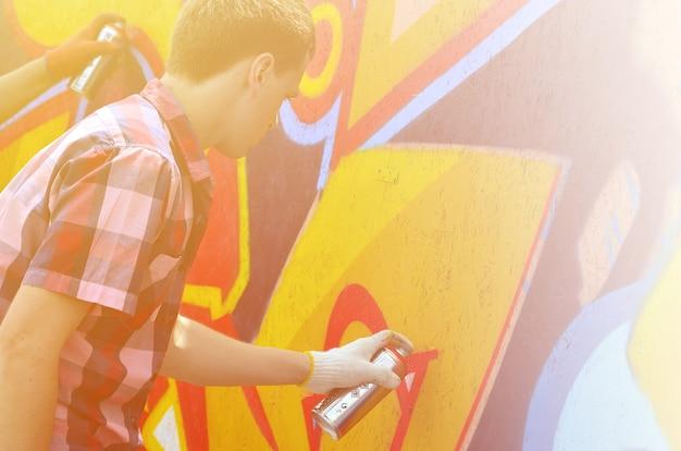 Un jeune graffeur aux cheveux roux peint un nouveau graffiti sur le mur