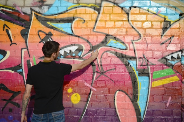 Jeune graffeur avec sac à dos et masque à gaz sur son cou peint des graffitis colorés