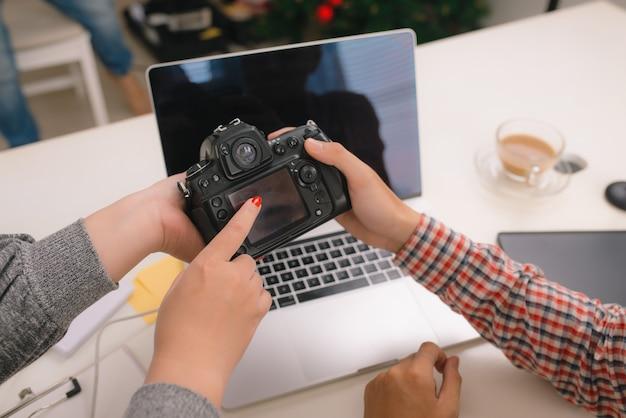 Jeune graphiste expliquant ses idées à son collègue avec appareil photo