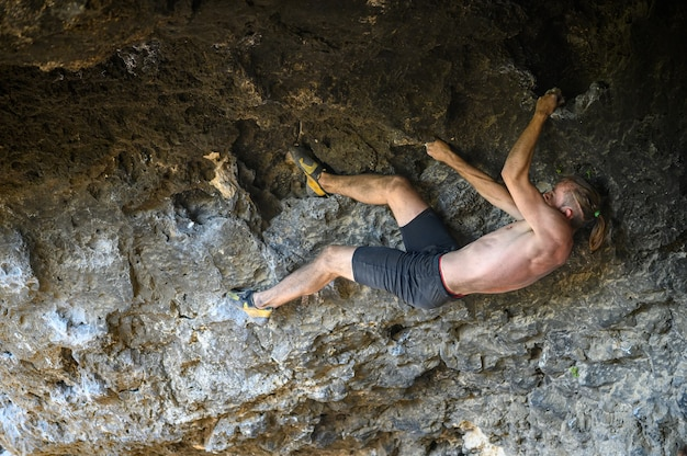 Jeune grimpeur mâle bouldering une paroi rocheuse dans une grotte