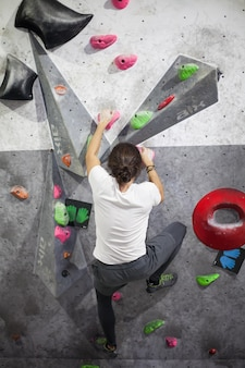 Jeune grimpeur mâle en forme remontant sur une paroi rocheuse, escalade sur un mur artificiel à l'intérieur