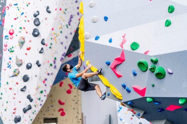 Un jeune grimpeur pratiquant l'escalade sur un mur d'escalade.