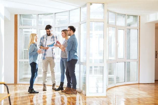 Jeune groupe de gens d'affaires dévoués dans le couloir de bureau discutant des graphiques commerciaux tout en buvant du café.