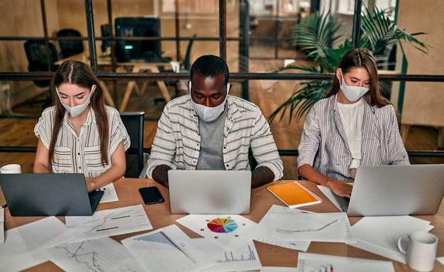 Un jeune groupe de gens d'affaires multiethniques portant des masques de protection travaille sur des ordinateurs portables dans un bureau moderne.
