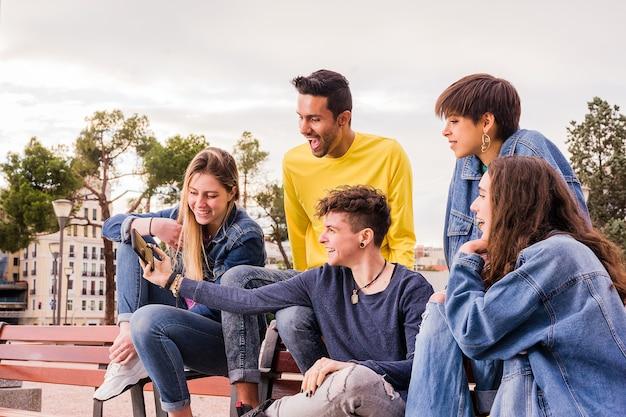 Un jeune groupe multiethnique au mode de vie ethnique diversifié multiracial prend un selfie avec un téléphone portable