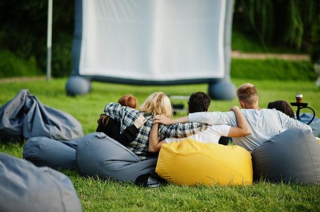 Jeune groupe multiethnique de personnes regardant un film à pouf dans un cinéma en plein air.