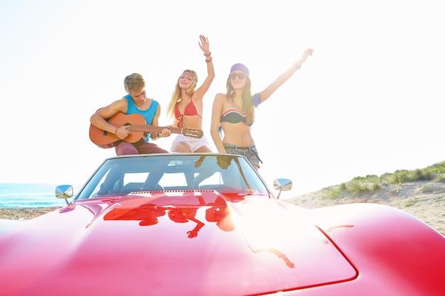 Jeune groupe s'amuser sur la plage, jouer de la guitare