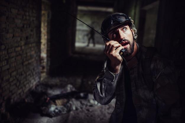Un jeune guerrier barbu parle à une radio portable.