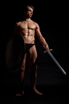 Jeune guerrier avec bouclier isolé sur fond noir.