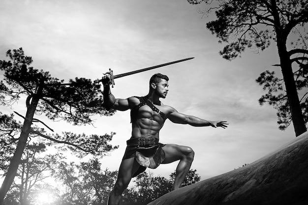 Jeune guerrier musclé avec une épée dans les montagnes