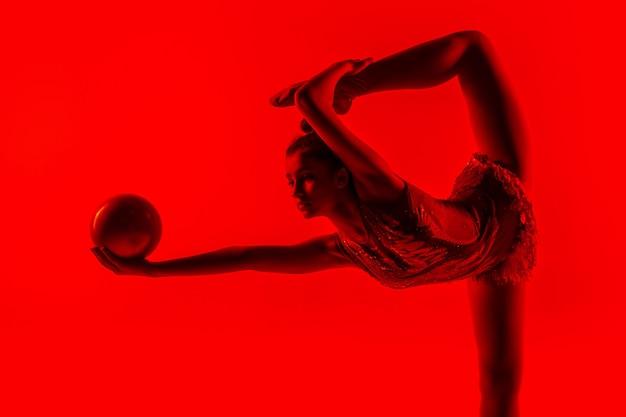 Jeune gymnaste féminine flexible isolée sur rouge