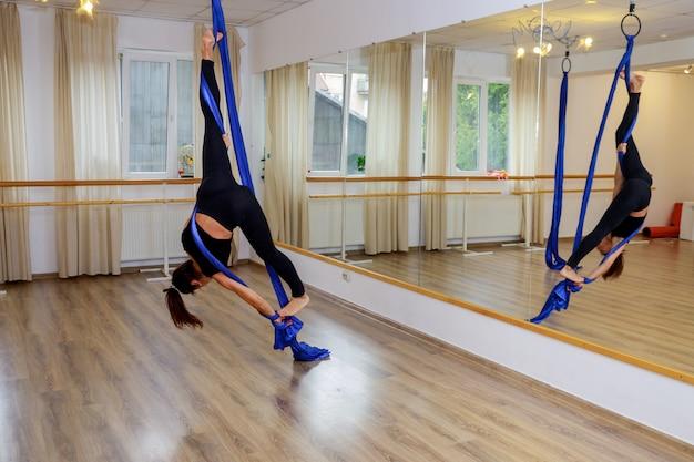 Jeune gymnaste femme faisant de la gymnastique sur corde dans la salle de fitness aérienne