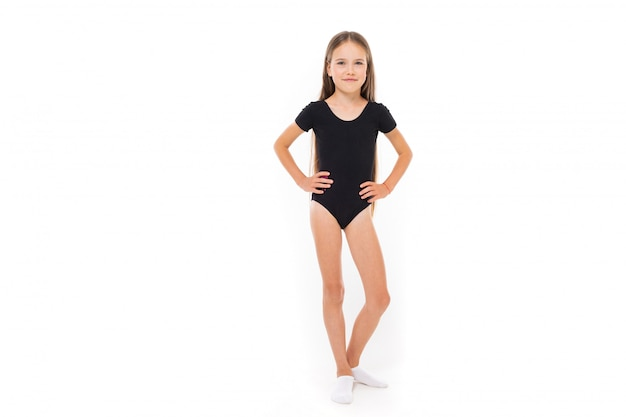 Jeune gymnaste en maillot de bain noir sur un mur blanc