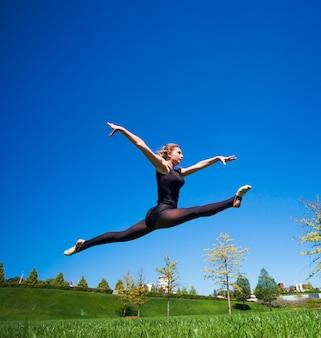 Jeune gymnaste souriante saute en deux et flotte au-dessus de la terre.