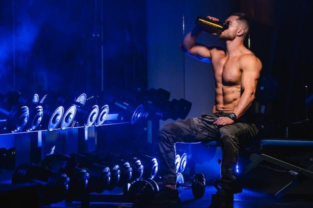 Jeune haltérophile bodybuilder beau sportif. homme avec un corps idéal, torse nu. boit de l'eau devant la caméra, muscles abdominaux, triceps biceps. fermer