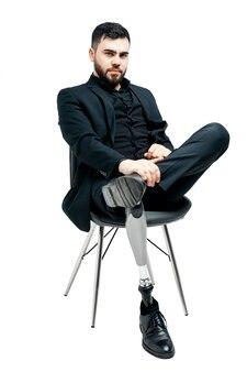 Jeune handicapé avec jambe prothétique, concept de membre artificiel. assis sur une chaise, isolé