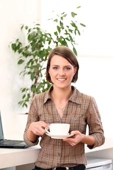 Jeune et heureuse femme avec une tasse de café
